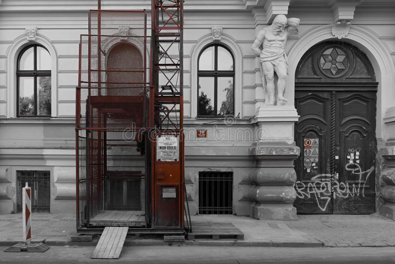 Zwart-witte oude muur met moderne rode lift in aanbouw stock fotografie