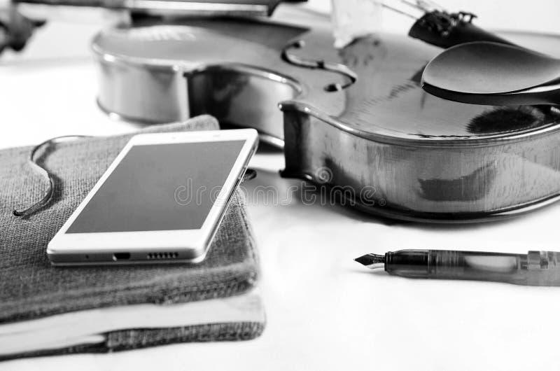 Zwart-witte pennota en viool op een witte oppervlakte stock afbeelding