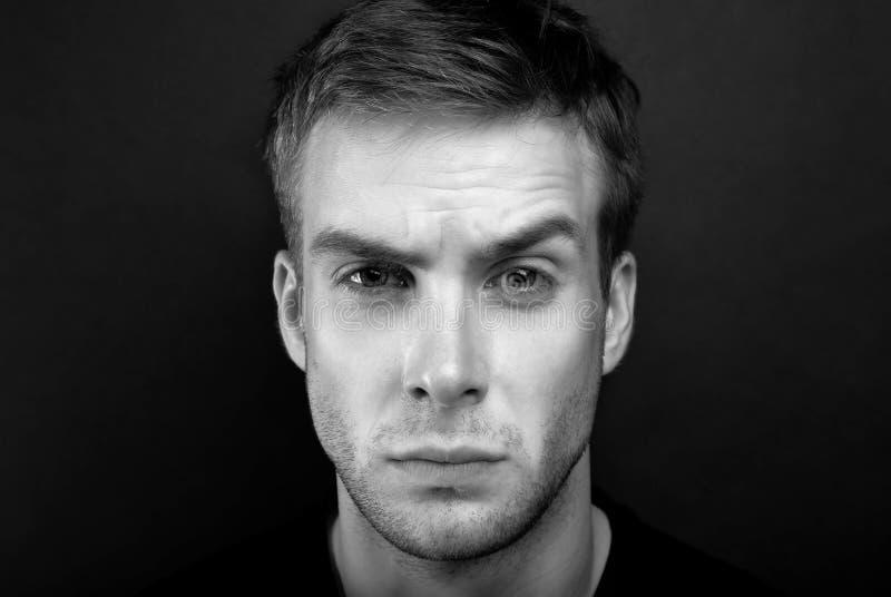 Zwart-witte portretfoto van de jonge mens met kwaad blik in v royalty-vrije stock fotografie