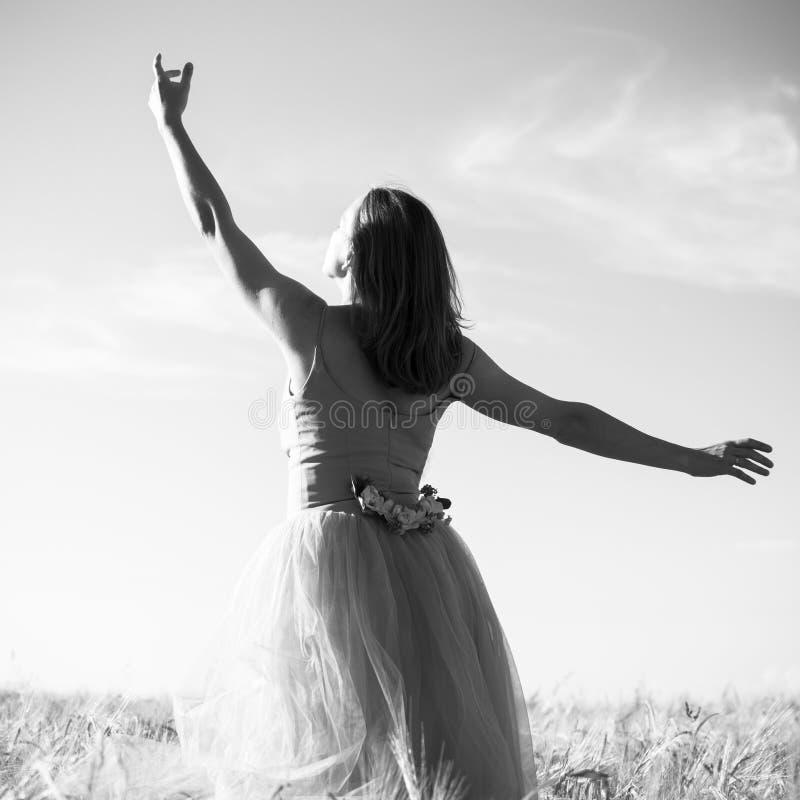 Zwart-witte romantische mooie jonge dame die pret hebben die op het gebied met hand tot de hemel op zich in openlucht achtergrond stock afbeelding