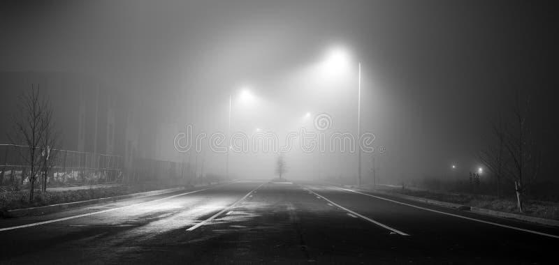 Zwart-witte straat bij nacht met mist stock afbeeldingen