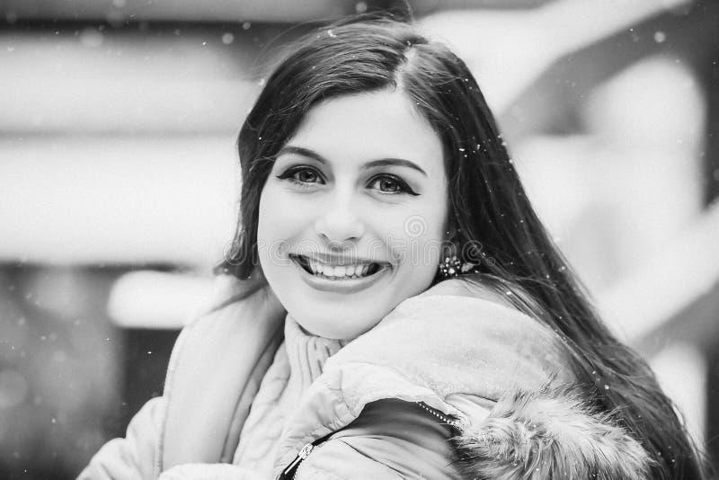 Zwart-witte tiener die buiten in sneeuw glimlachen stock fotografie