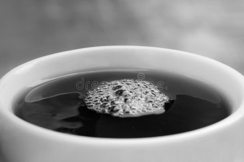 Zwart-witte verfrissende koffie/theekop met bellen op bovenkant, close-up, macro royalty-vrije stock fotografie