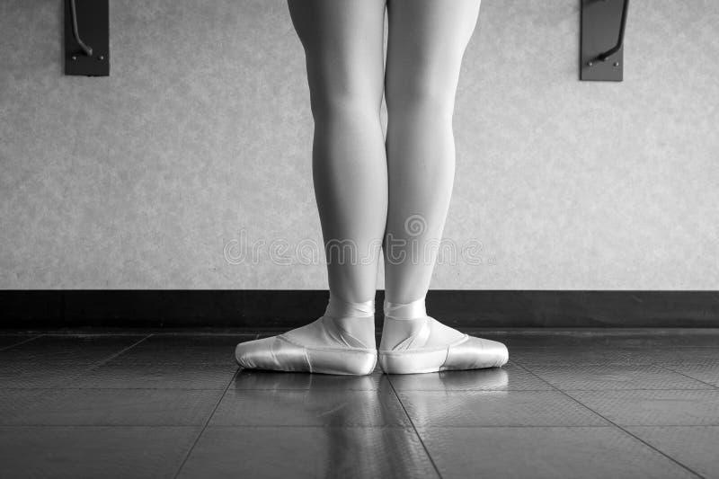 Zwart-witte versie van achtermening van balletdanserballerina bij de staaf in dansklasse die zich in eerste positie bevinden stock foto's