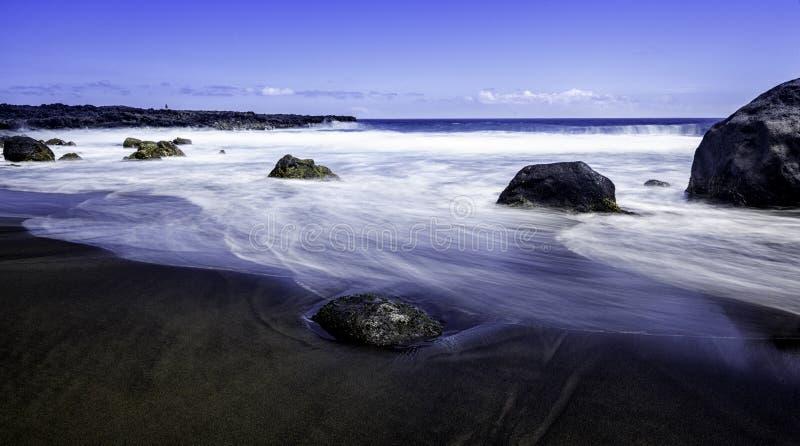 Zwart zandstrand. stock afbeeldingen