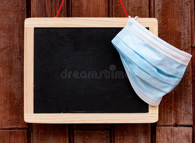 Zwartbord op de lege school met beschermingsmasker stock afbeeldingen