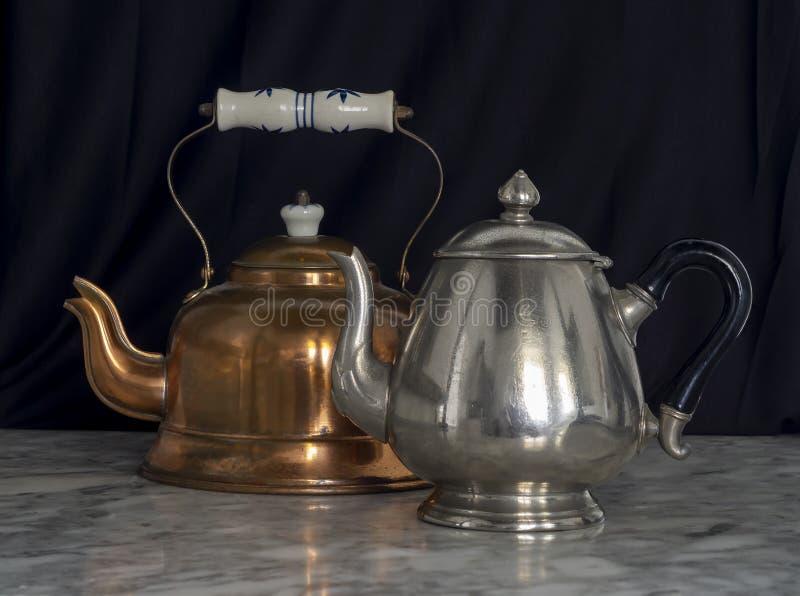Zwarte achtergrond-marmertabel met zilver en Brass Teapots stock fotografie