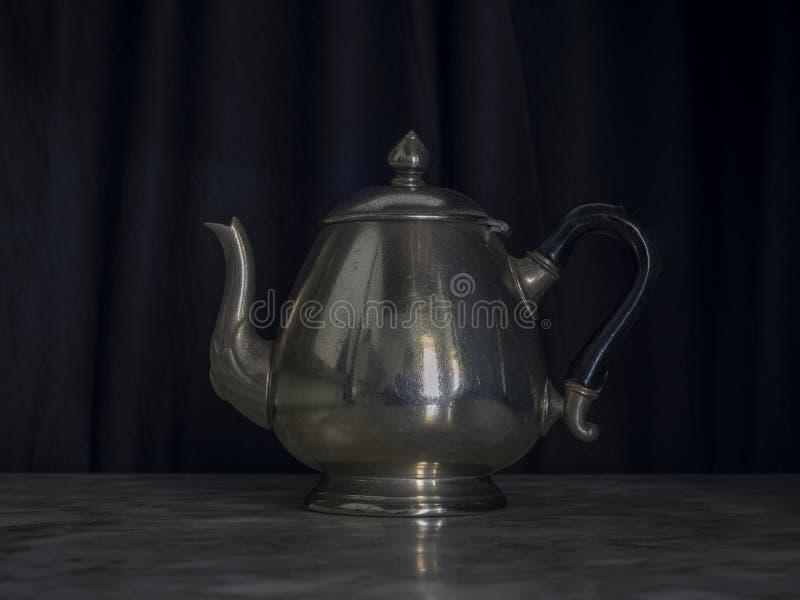 Zwarte achtergrond-marmertabel met zilver en Brass Teapots royalty-vrije stock afbeeldingen
