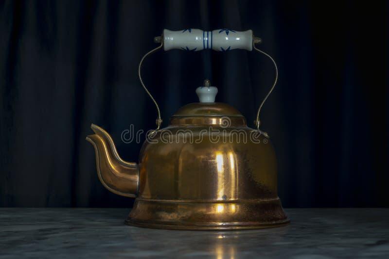 Zwarte Achtergrondafhandelingstabel van Brass Teapot stock fotografie