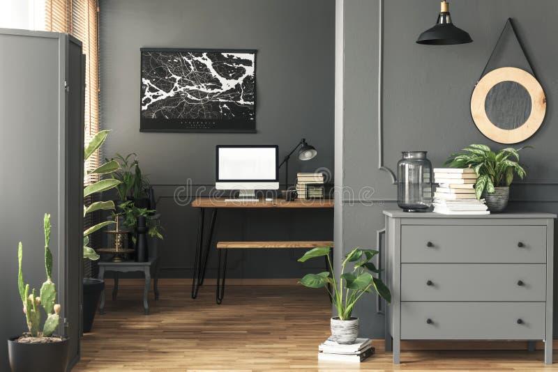 Zwarte affiche op grijze muur boven bureau met model in het binnenland van het huisbureau met spiegel Echte foto stock fotografie