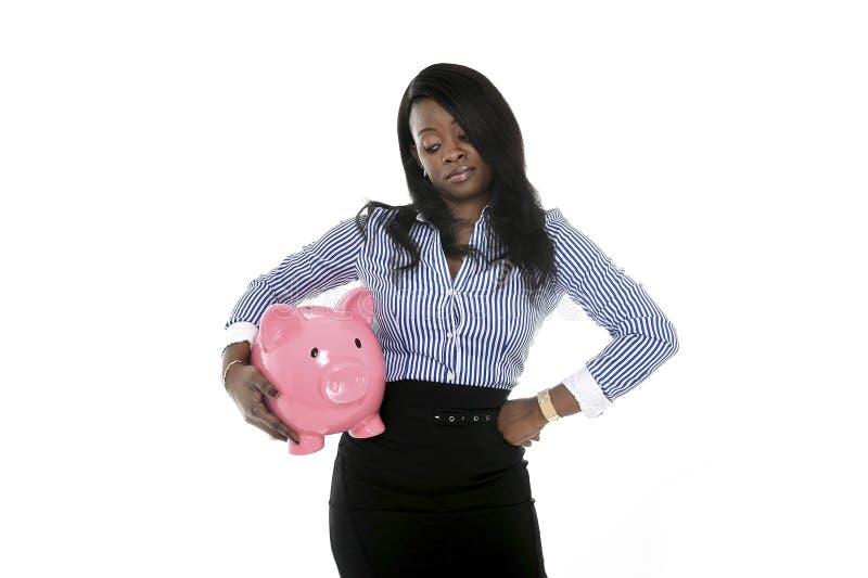 Zwarte Afrikaanse Amerikaanse bedrijfsvrouw die reusachtige roze piggybank houden stock afbeeldingen