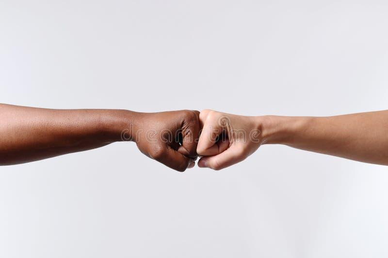 Zwarte Afrikaanse Amerikaanse ras vrouwelijke hand wat betreft gewrichten met witte Kaukasische vrouw in multiraciale diversiteit royalty-vrije stock afbeeldingen