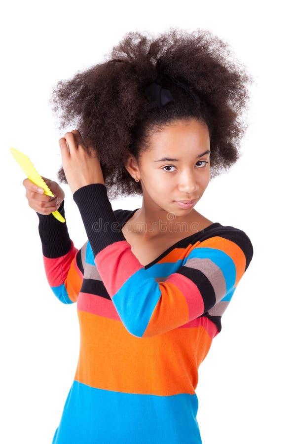 Zwarte Afrikaanse Amerikaanse tiener die haar afrohaar kammen stock afbeeldingen