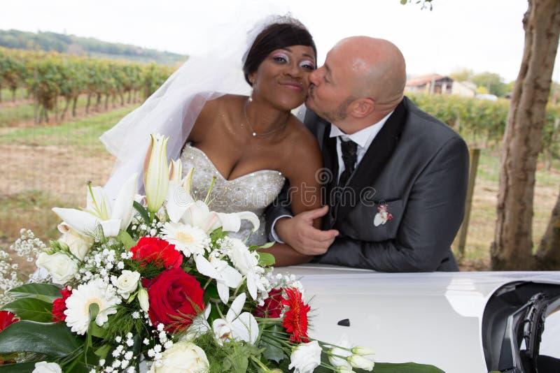 Zwarte Afrikaanse bruidkus door Kaukasische Amerikaanse bruidegom met huwelijksauto royalty-vrije stock foto's
