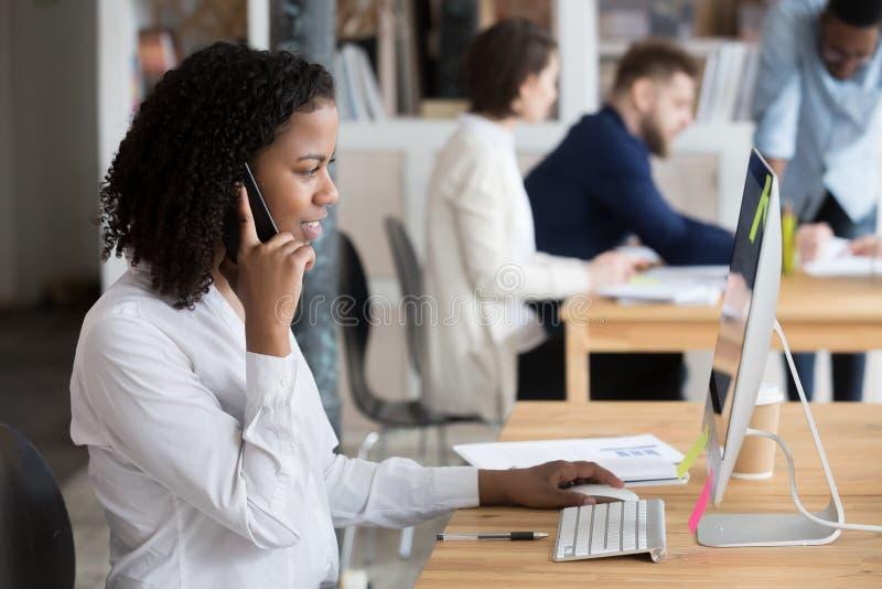 Zwarte Afrikaanse werknemer die op telefoonzitting bij bureau spreken royalty-vrije stock foto's