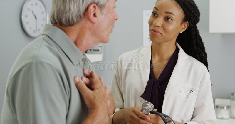 Zwarte arts die aan bejaarde geduldige ademhaling luisteren royalty-vrije stock afbeeldingen