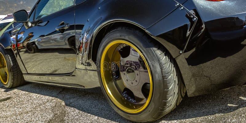 Zwarte auto met gouden wielrand en zwarte spokes royalty-vrije stock foto
