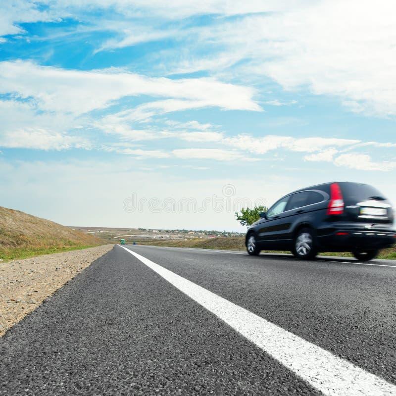 Zwarte auto in motie op asfaltweg en wolken royalty-vrije stock foto
