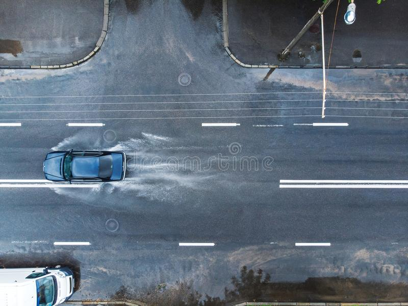 Zwarte autoplonsen door watervulklei op overstroomde straat Aeria royalty-vrije stock fotografie