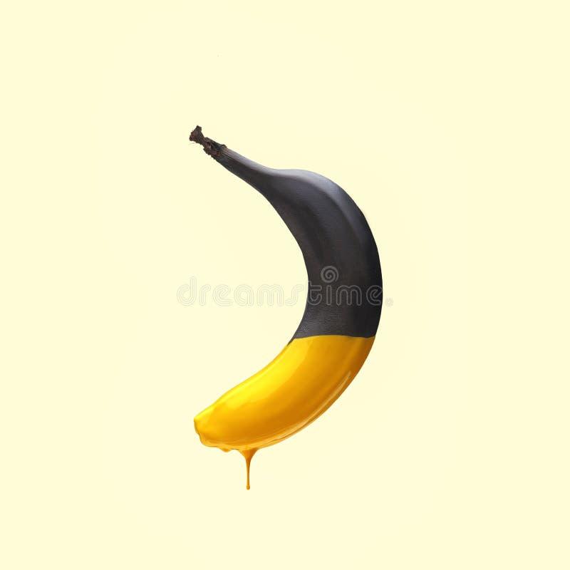 Zwarte banaan met druipende gele verf op lichtgele achtergrond Creatief voedselconcept royalty-vrije stock afbeeldingen