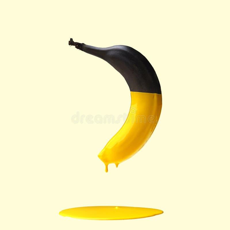Zwarte banaan met druipende gele verf op lichtgele achtergrond Creatief voedselconcept stock afbeelding