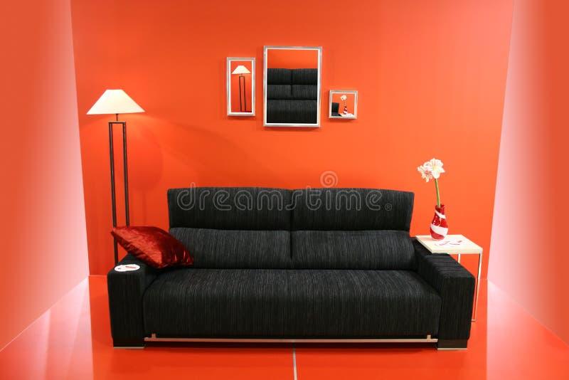 Zwarte bank op rode muur stock fotografie