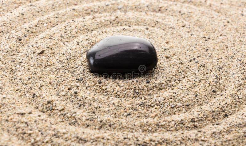 Zwarte basaltsteen op zand die waterrimpelingen imiteren royalty-vrije stock afbeelding