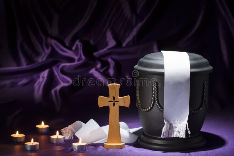 Zwarte begraafplaats urnk met kruis en kaarsen en wit lint op donkerpaarse achtergrond royalty-vrije stock foto's