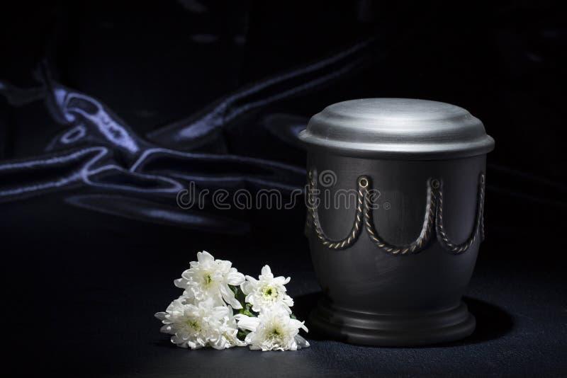 Zwarte begraafplaatsurn met witte chrysant, op diepe blauwe achtergrond stock afbeelding
