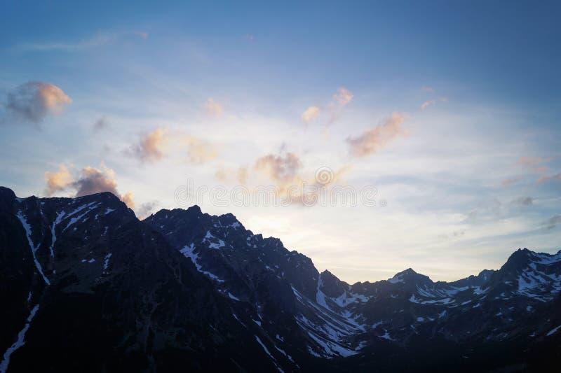 Zwarte berg met witte sneeuw onder de blauwe hemel stock fotografie