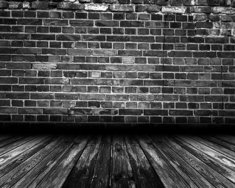 Zwarte binnenlandse ruimte met bakstenen muur en houten vloer stock foto's