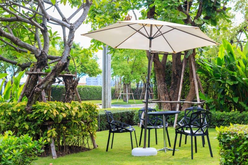 Zwarte bureaustoel onder de witte paraplu op het gras royalty-vrije stock afbeelding