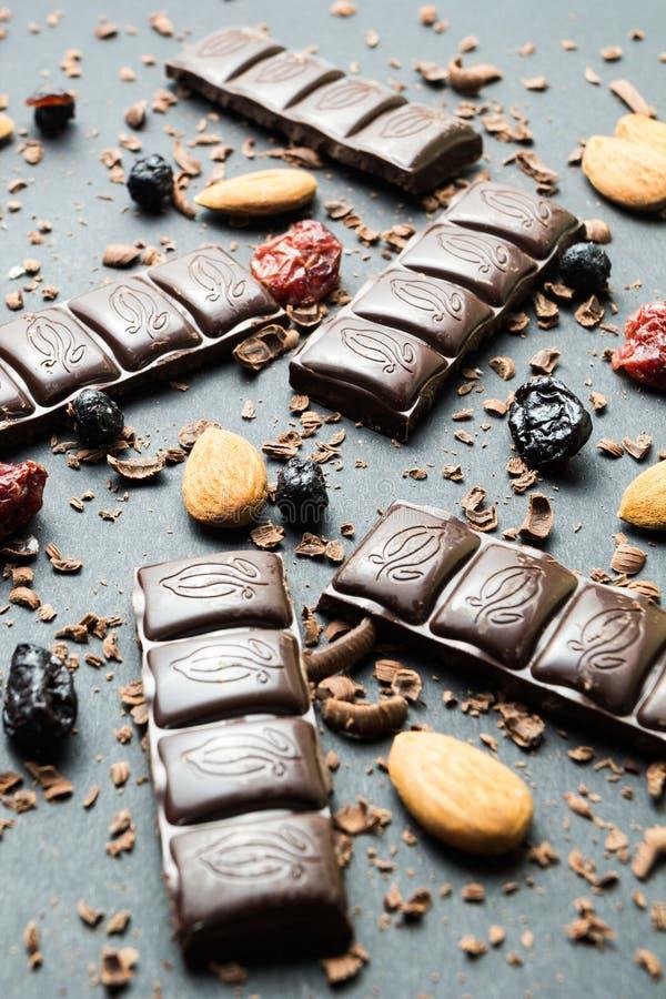 Zwarte chocolade met droge vruchten op een zwarte achtergrond, verticaal royalty-vrije stock foto's