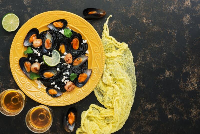 Zwarte deegwarenspaghetti met mosselen, kammosselen en witte wijn op een rustieke achtergrond Mediterraan voedsel Hoogste mening, stock fotografie