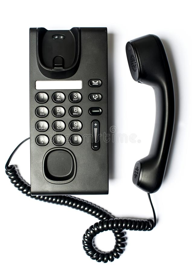 Zwarte die Bureautelefoon op witte achtergrond wordt ge?soleerd stock afbeelding
