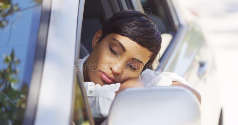 Zwarte die hoofd uit autoraam rusten stock foto's