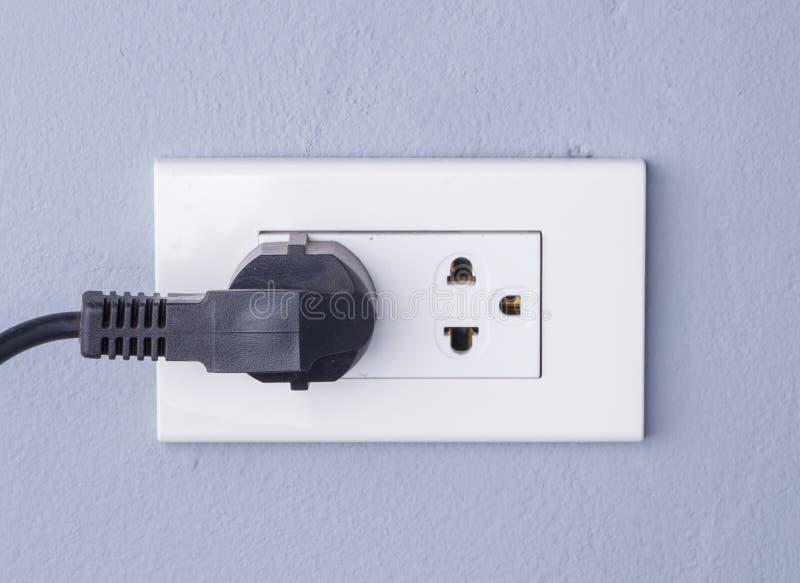 Zwarte die kabel in een witte elektrische afzet opgezet op grijs w wordt gestopt stock fotografie