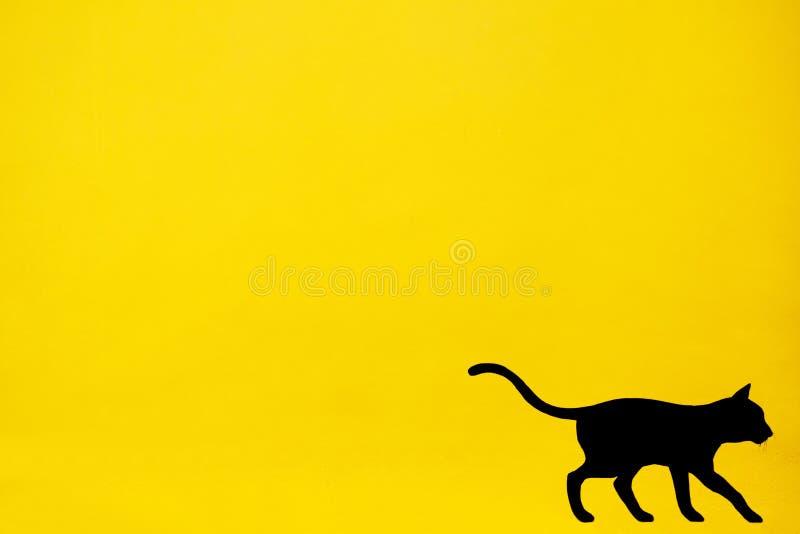 Zwarte die kat op gele muur wordt geschilderd stock fotografie