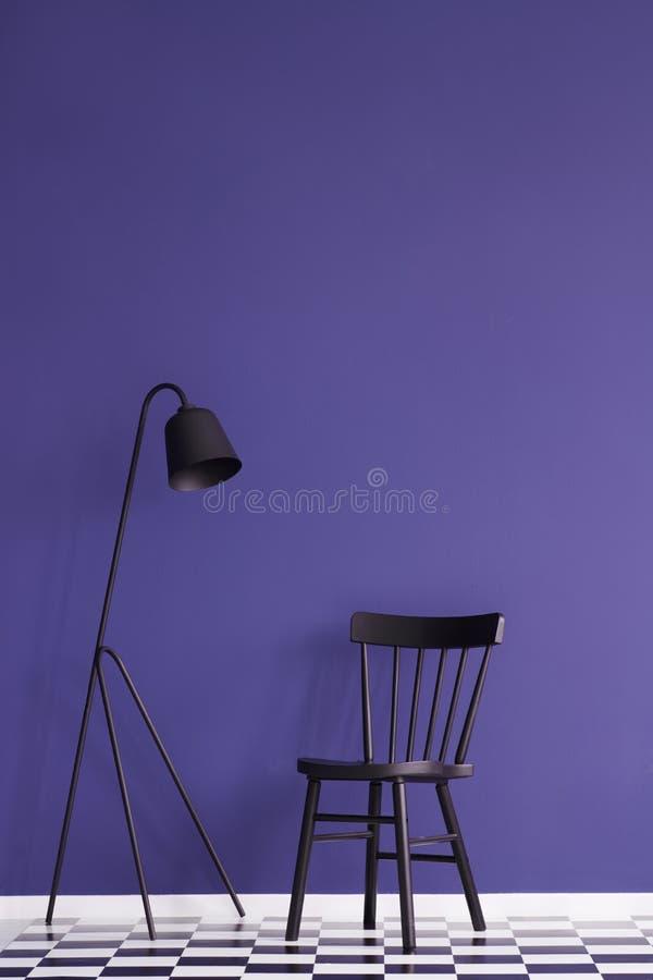 Zwarte die lamp en stoel op een violette muur in eenvoudige woonkamer wordt geplaatst royalty-vrije stock foto