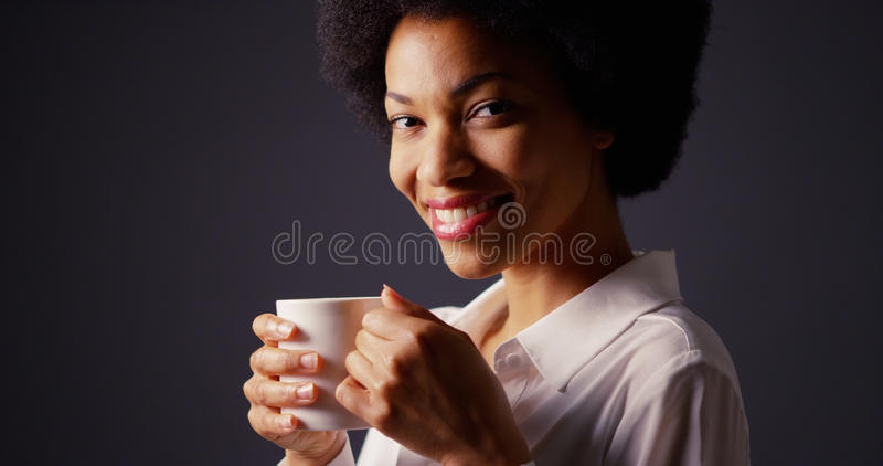 Zwarte die met afro in studio hete koffie en het glimlachen drinken royalty-vrije stock foto's