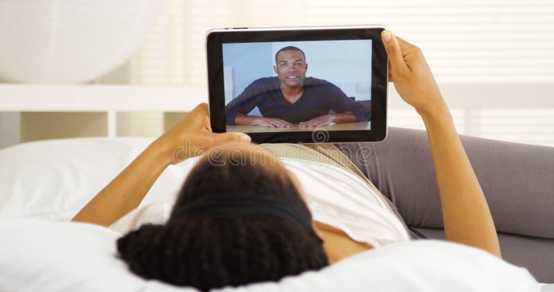 Zwarte die met vriend op tablet spreken stock fotografie