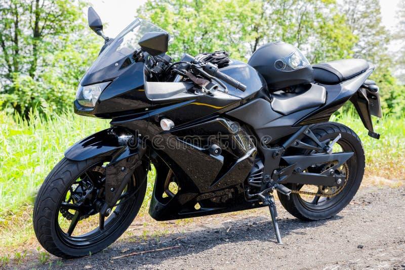 Zwarte die motobike op de kant van de weg wordt geparkeerd stock fotografie
