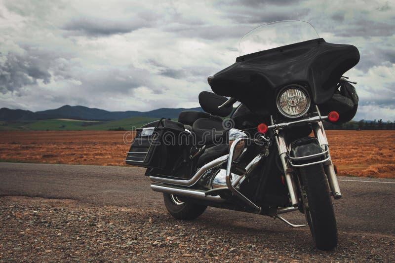 Zwarte die motorfiets bij de landweg wordt geparkeerd royalty-vrije stock fotografie