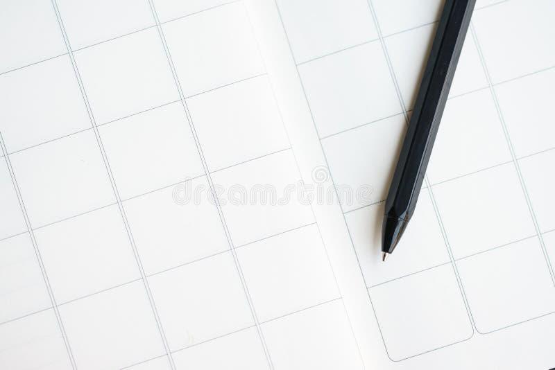 Zwarte die pen op een blocnote met het patroon van het bloknet wordt geplaatst stock foto's