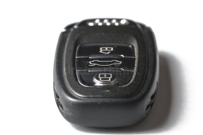 Zwarte die sleutel van een auto op een witte achtergrond wordt ge?soleerd Gelukkige mens met nieuwe autosleutel stock fotografie