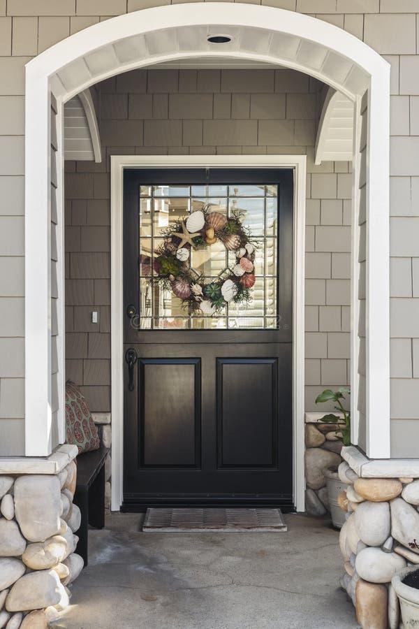 Zwarte die voordeur van een huis door een boog wordt gezien royalty-vrije stock foto's