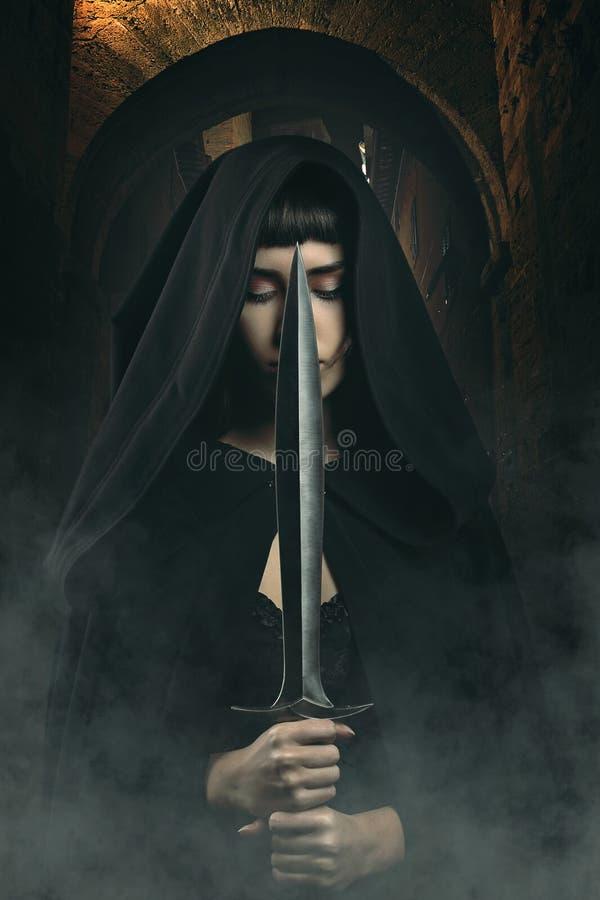 Zwarte dief met een kap met mes in donkere dorpssteeg stock foto's
