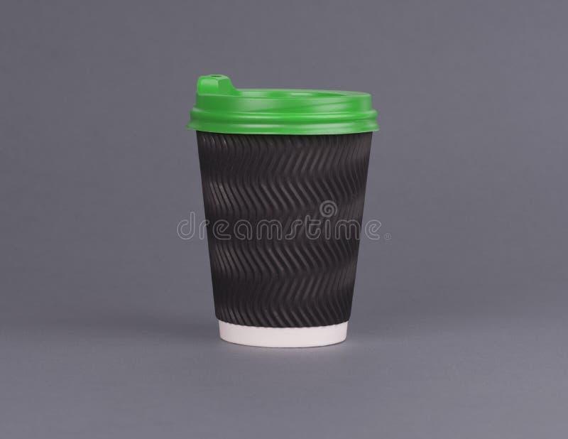 Zwarte document koffiekop met een groen deksel op een grijze achtergrond Een Kop van koffie om te gaan model royalty-vrije stock afbeeldingen