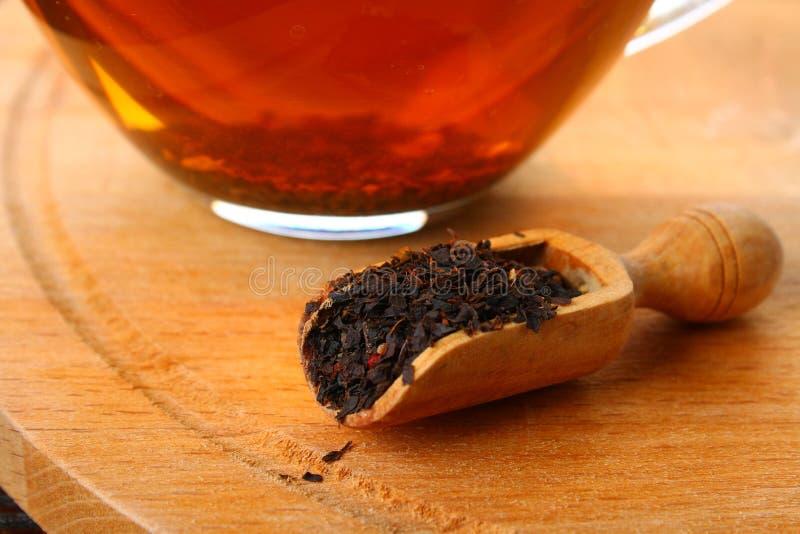 Zwarte droge thee met een kers in een lepel op een houten lijst stock foto