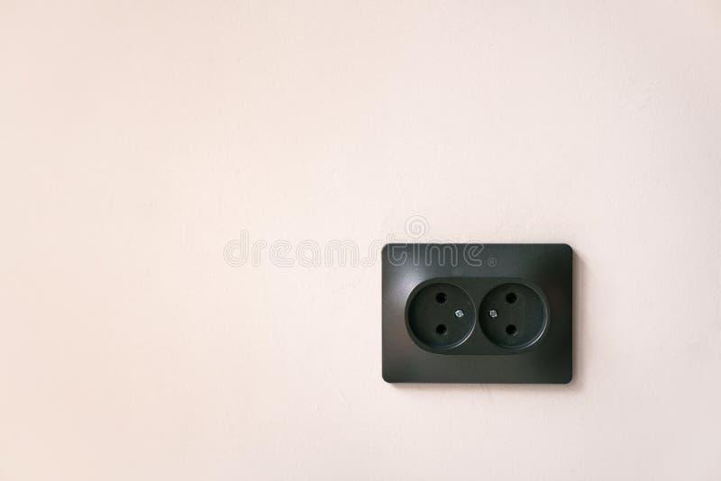 Zwarte dubbele elektroafzet op een lichtrose muur stock foto's
